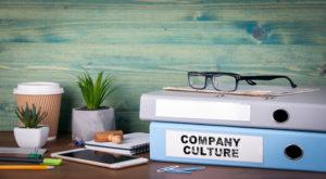 - Cultura Assertiva Vera Martins 300x165 - Company Culture. Binders on desk in the office. Business background.